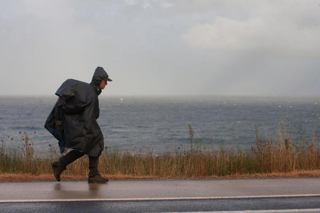 Un peregrino realiza el Camino de la Costa en Galicia cubierto contra...