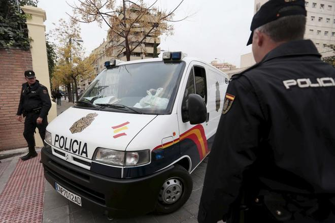 Agentes de la Policía Nacional vigilan la llegada de un furgón con...