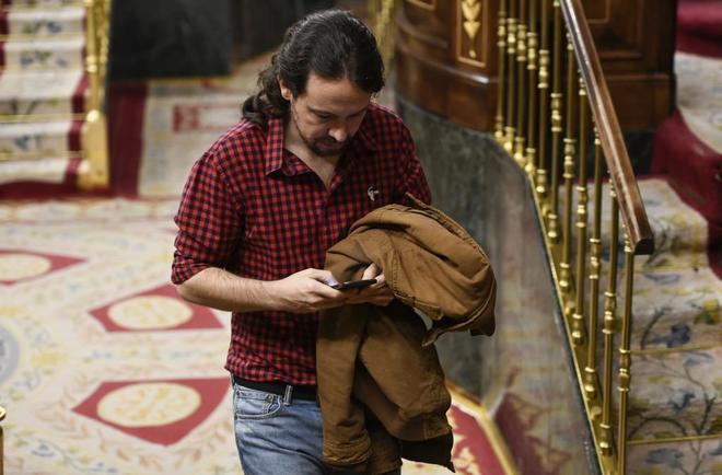 El secretario general de Podemos, Pablo Iglesias, consulta su móvil en el Congreso