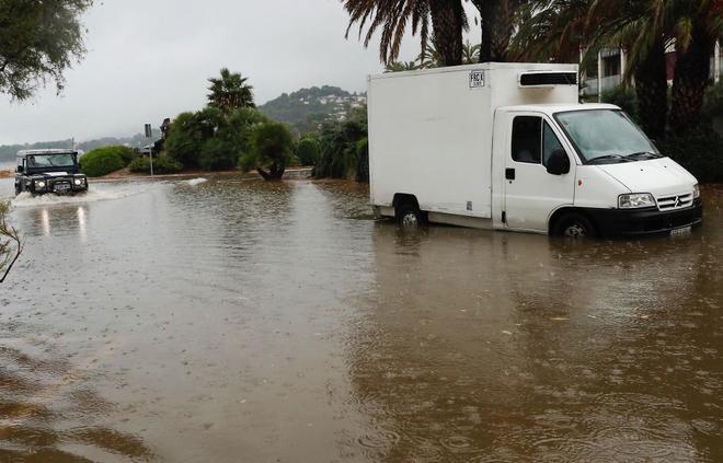 Un camión circula por una calle anegada en Denia (Alicante) por la lluvia caída.