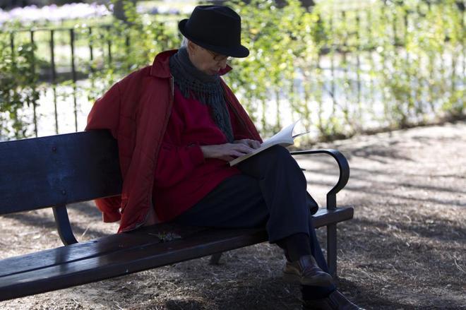 Una jubilada lee un libro en el Parque Oeste de Madrid.