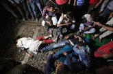 Los familiares de las víctimas lloran junto a sus cuerpos tras el...