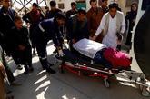 Sanitarios afganos trasladan al hospital a una mujer herida por una...