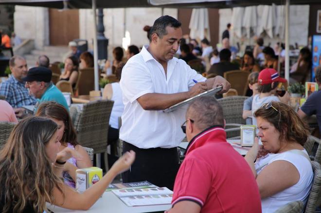 Un camarero atiende una terraza en Valencia.