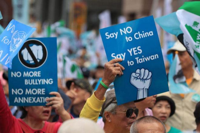Independentistas de Taiwan muestran carteles contra China.