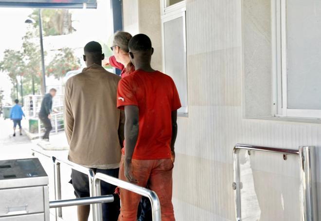 Efectivos de la Policía trasladan a dos inmigrantes que saltaron la...