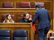 El secretario general de Podemos, Pablo Iglesias, conversa con el líder de IU, Alberto Garzón, hoy, en el Congreso.