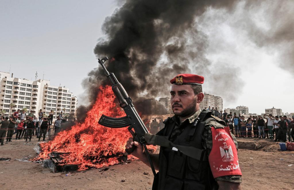 Un miembro de Hamas hace guardia mientras otros queman drogas confiscadas en Gaza.