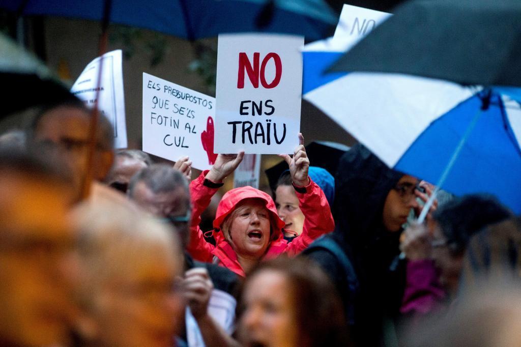"""Participantes en la protesta de los CDR frente a la sede de Esquerra Republicana de Catalunya, para reivindicar el fin del autonomismo, muestran un cartel con el lema """"No ens Traiu"""" (no nos traicionéis)."""