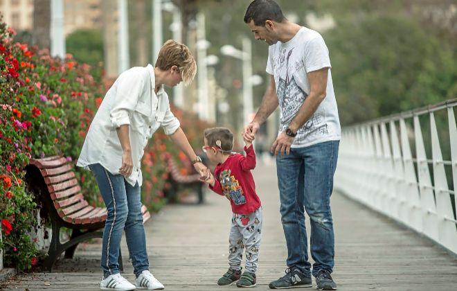 Jose y Esther, con el pequeño Marc, pasean por el Puente de las Flores de Valencia.