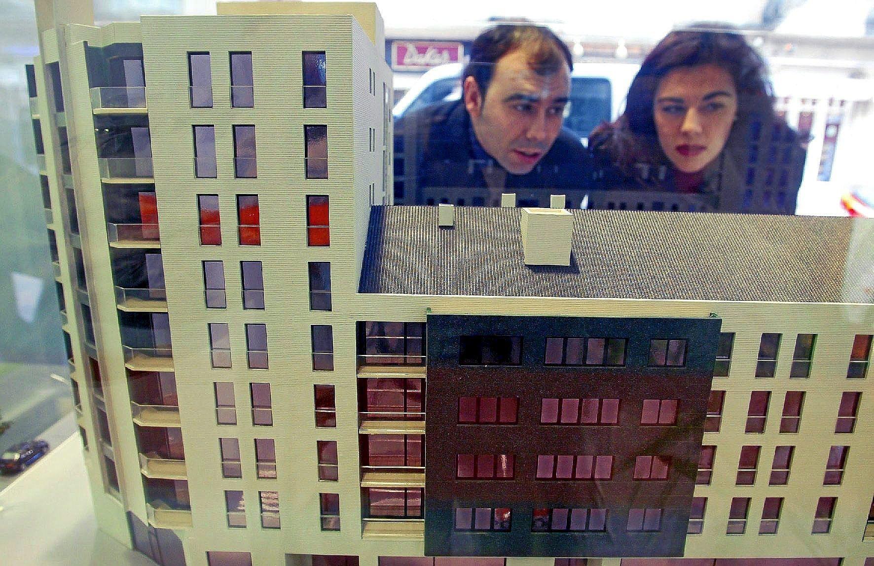 Una pareja examina la maqueta de un bloque de viviendas en venta.