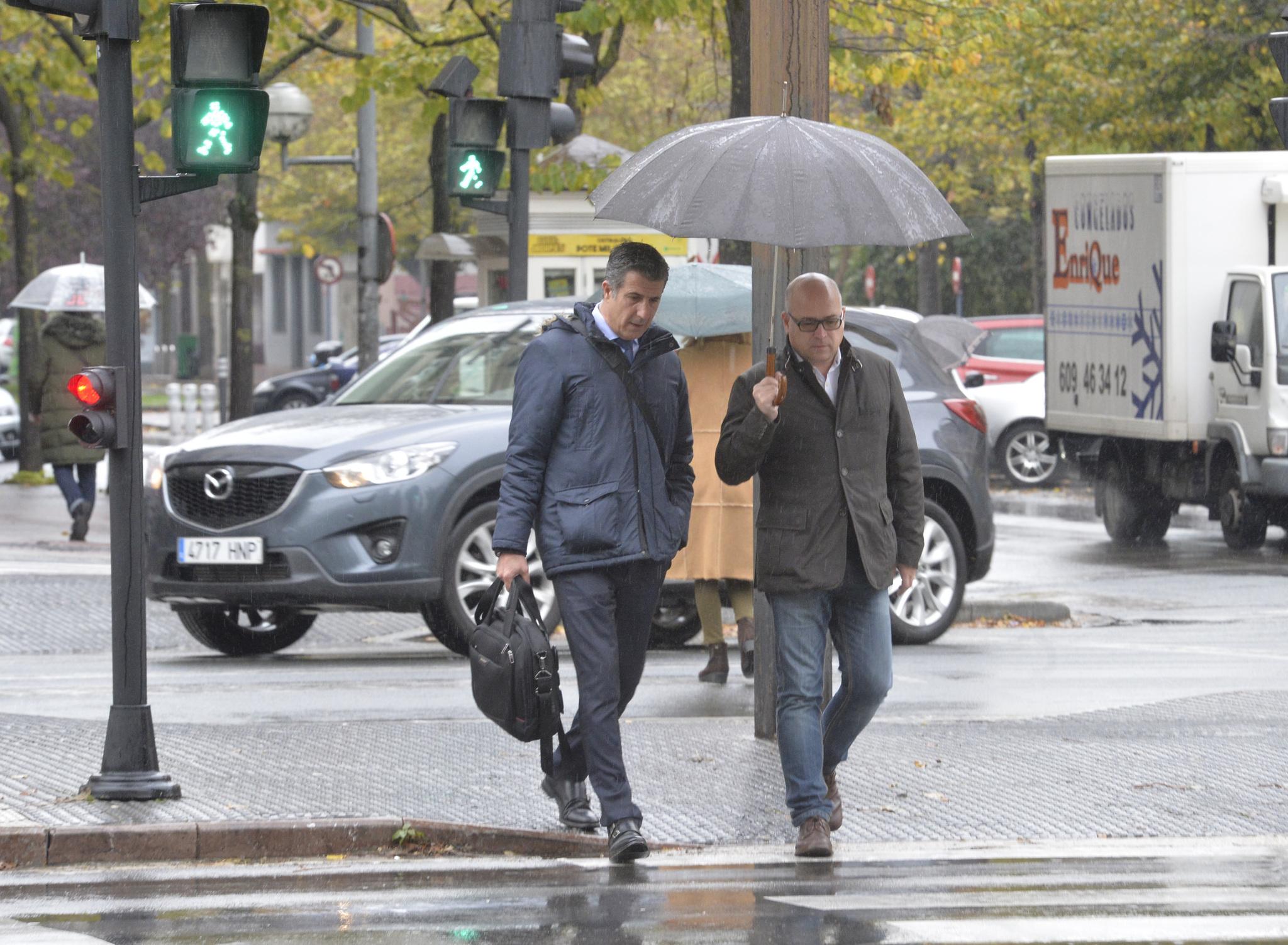 Alfredo De Miguel cubre con su paraguas a su abogado Gonzalo Susaeta antes de la vista de hoy.