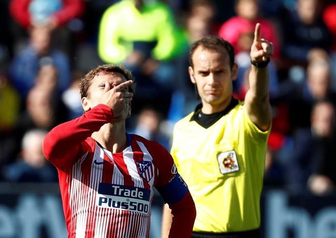 Antoine Griezmann se lleva la mano a la cara junto al árbitro.
