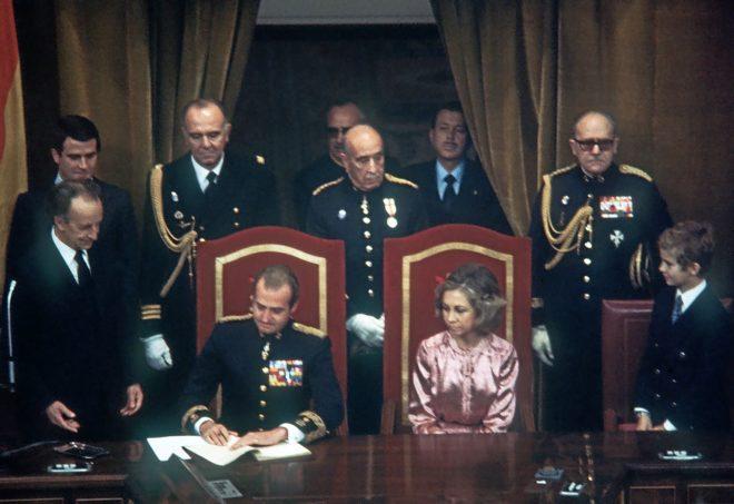 Don Juan Carlos procede a la sanción de la Constitución, en el Congreso, el 27 de diciembre de 1978, ante Doña Sofía y el entonces Príncipe Felipe
