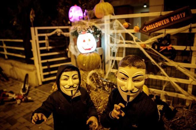Niños portan máscaras de Guy Fawkes durante las celebraciones de Halloween