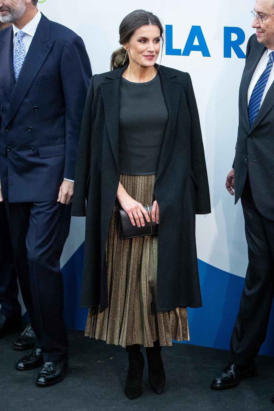Para asistir al evento, Doña Letizia eligió una falda plisada dorada...
