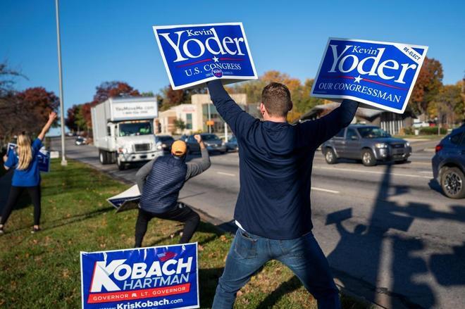 Voluntarios para la campaña de Kevin Yoder muestran pancartas para apoyar al candidato republicano en Overland Park, Kansas.