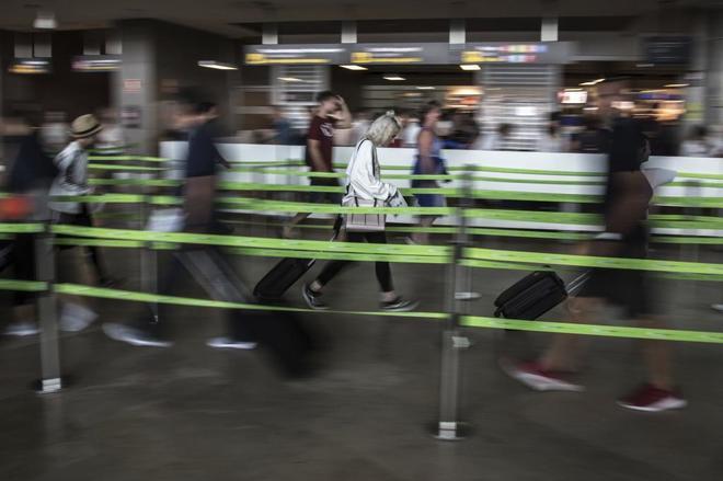 Gente en los controles de acceso de aeropuerto de Valencia.