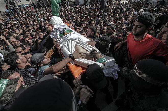 Combatientes del brazo armado de Hamas portan el cuerpo de un compañero en la Franja de Gaza.