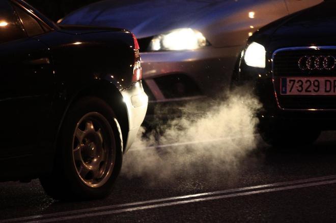 Humo contaminante entre dos coches que circulan por Madrid.