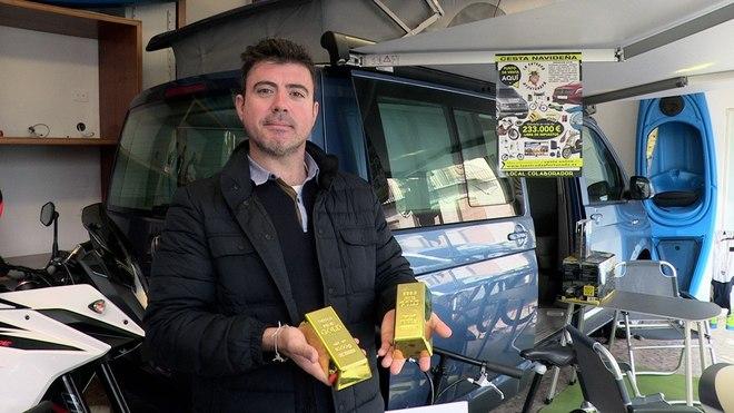 El promotor de esta iniciativa, Javier Piquer, muestra dos lingotes de oro incluidos en la cesta.