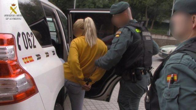 Los agentes trasladando a una de los detenidos.
