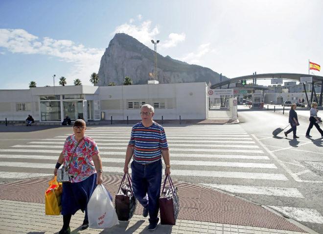 Dos personas abandonan Gibraltar por la frontera española de La Línea de la Concepción.
