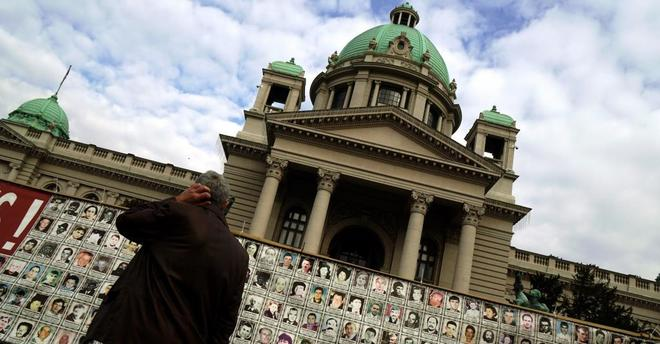 Un hombre observa fotografías de los desaparecidos durante la Guerra...