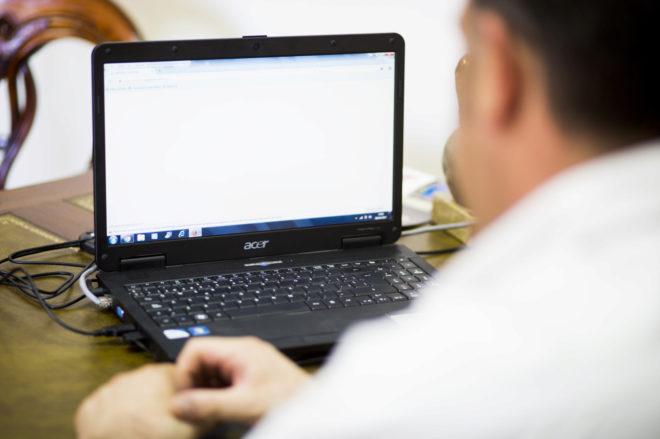 Un hombre observa la pantalla de su portátil.