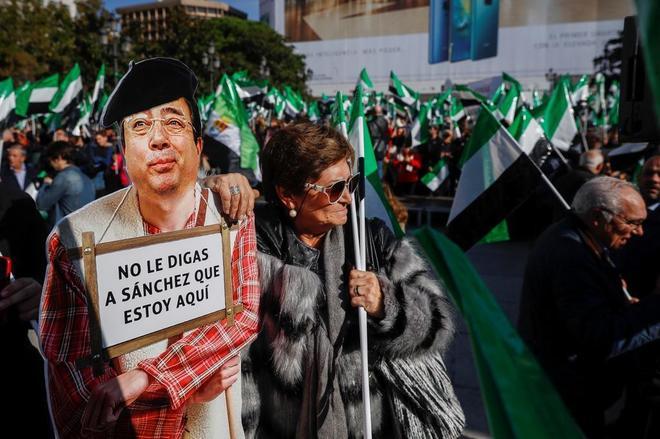 Una manifestante exhibe una foto crítica con la ausencia del presidente de Extremadura, Guillermo Fernández Vara.