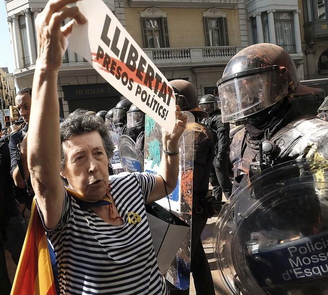Una manifesante independentista delante de los Mossos en Barcelona, protestando contra la marcha de Jusapol en septiembre.