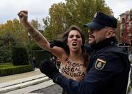 Una integrante de Femen se rebela mientras un agente de la Policía intenta interceptarla.