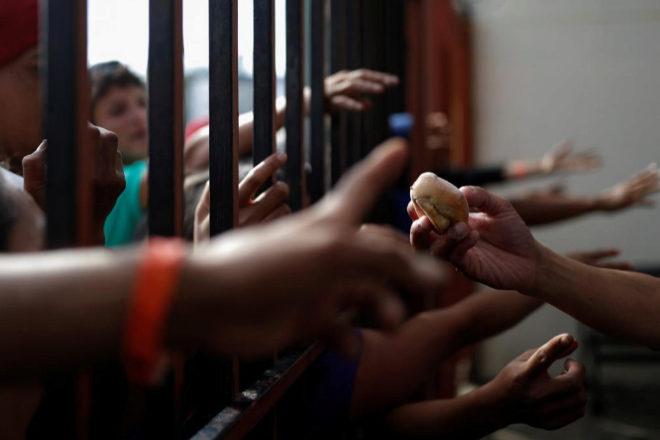 Integrantes de la caravana intentan obtener un trozo de pan en Tijuana, México.