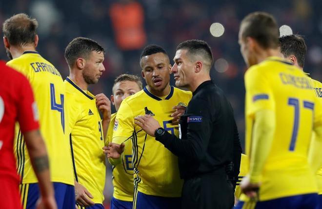 El árbitro Istvan Kovacs habla con el delantero sueco Marcus Berg.