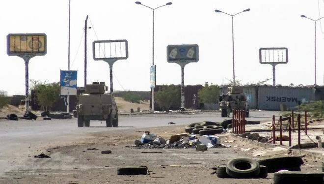 Vehículos de las tropas gubernamentales vigilan un parque industrial destruido de Hodeida, este domingo
