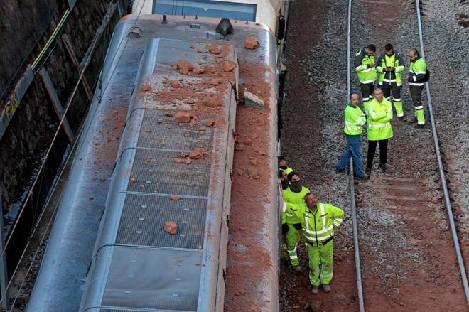 Técnicos y operarios de Adif realizando las tareas para retirar los convoyes que quedaron en la vía ferroviaria.