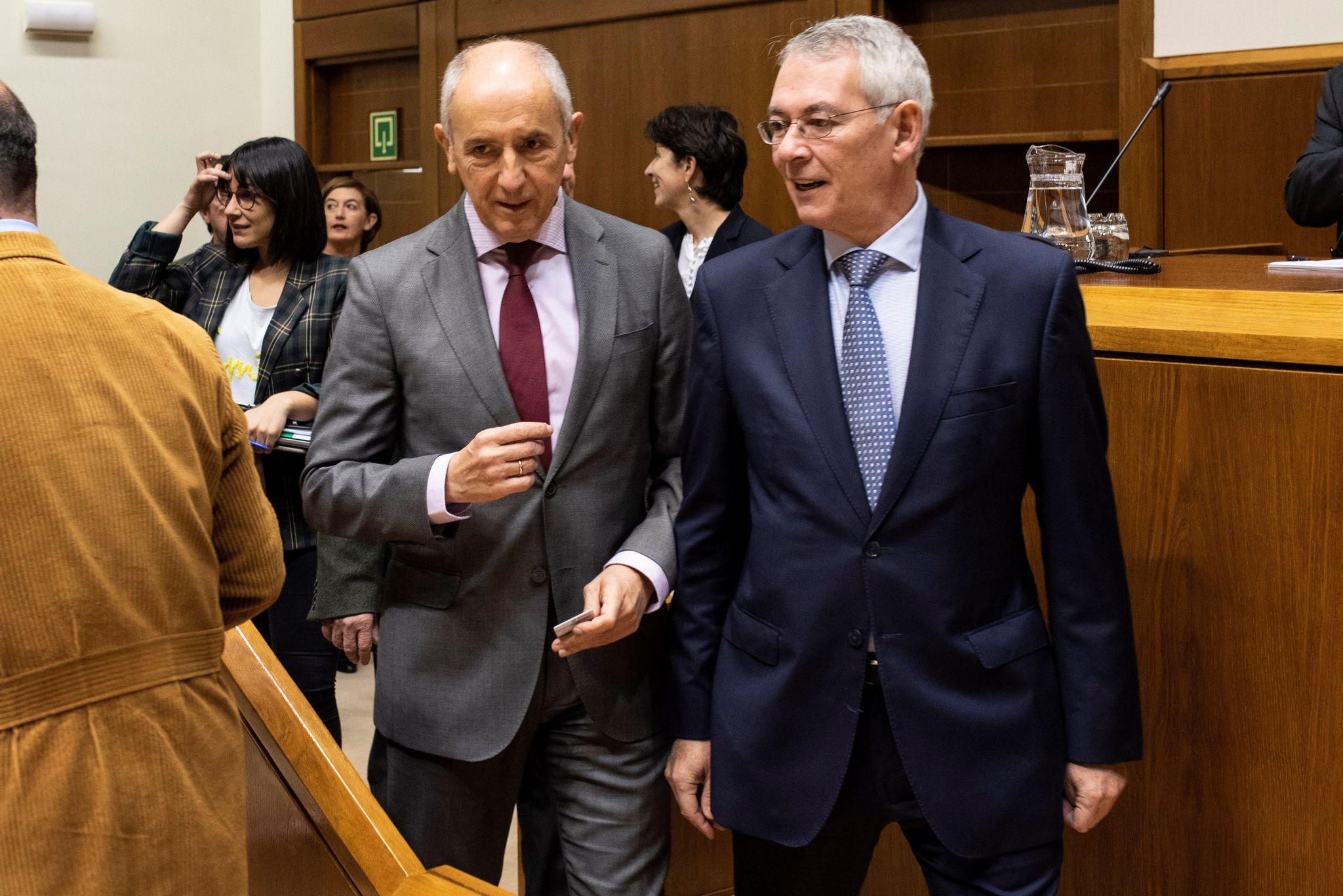 Antón Damborenea conversa con el consejero Josu Erkoreka durante el pleno del Parlamento Vasco.