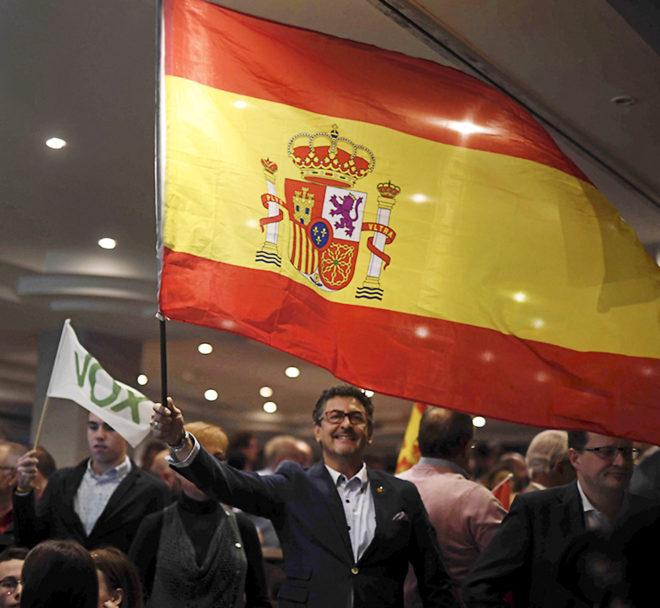 Un asistente a un acto de Vox en Córdoba porta una bandera española