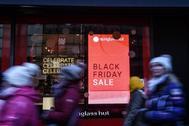 Ciudadanos neoyorquinos pasan por delante de una tienda que anuncia el Black Friday