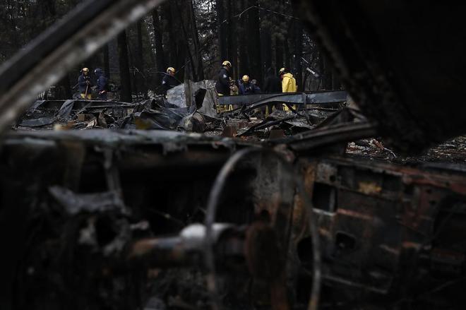 Los bomberos trabajan entre escombros y coches arrasados por las...