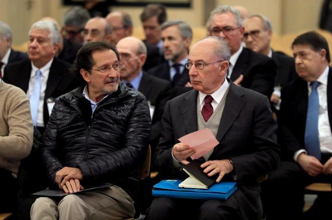 Rodrigo Rato, sentado junto a J. A. Moral Santín, sujeta un papel esta mañana en el juicio de Bankia.