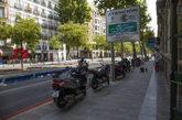 Imagen de varias motos frente a un cartel de Madrid Central