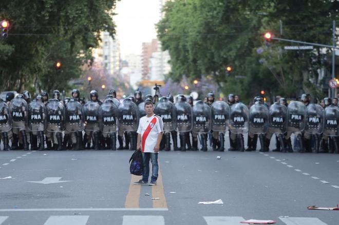 Un aficionado de River, con las fuerzas de seguridad a su espalda.