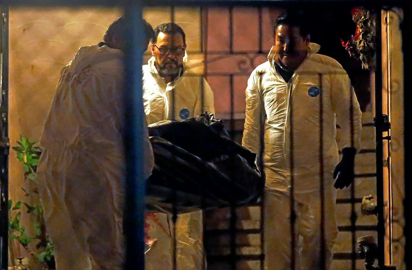 Expertos forenses portan uno de los seis cadáveres encontrados en el interior de un apartamento en Arboledas del Sur, Guadalajara (México).