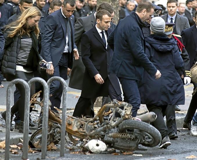 El presidente galo, Emmanuel Macron, comprueba los daños tras la violencia en las calles de París el sábado.