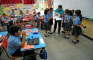 Una profesora examina un libro con un grupo de alumnos en el colegio.