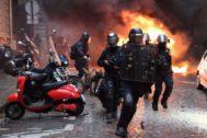 Antidisturbios corren junto a un coche incendiado en las violentas protestas que ayer sacudieron París.