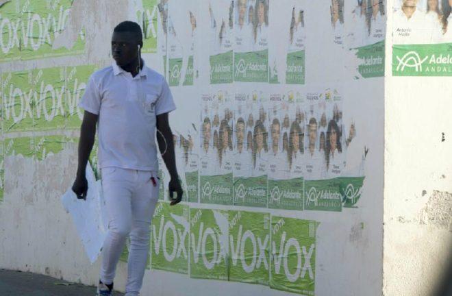 Un inmigrante, en Campohermoso, Níjar (Almería) ante carteles electorales de Vox.