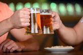 Dos hombres brindan con sendas jarras de cerveza.
