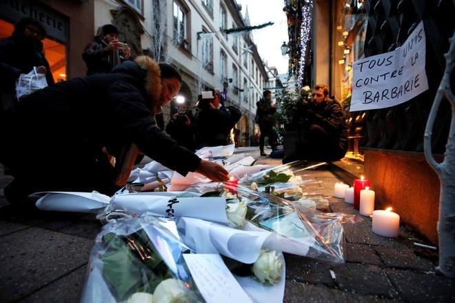 Ciudadanos encienden velas en el lugar donde falleció una de las víctimas del ataque en Estrasburgo.